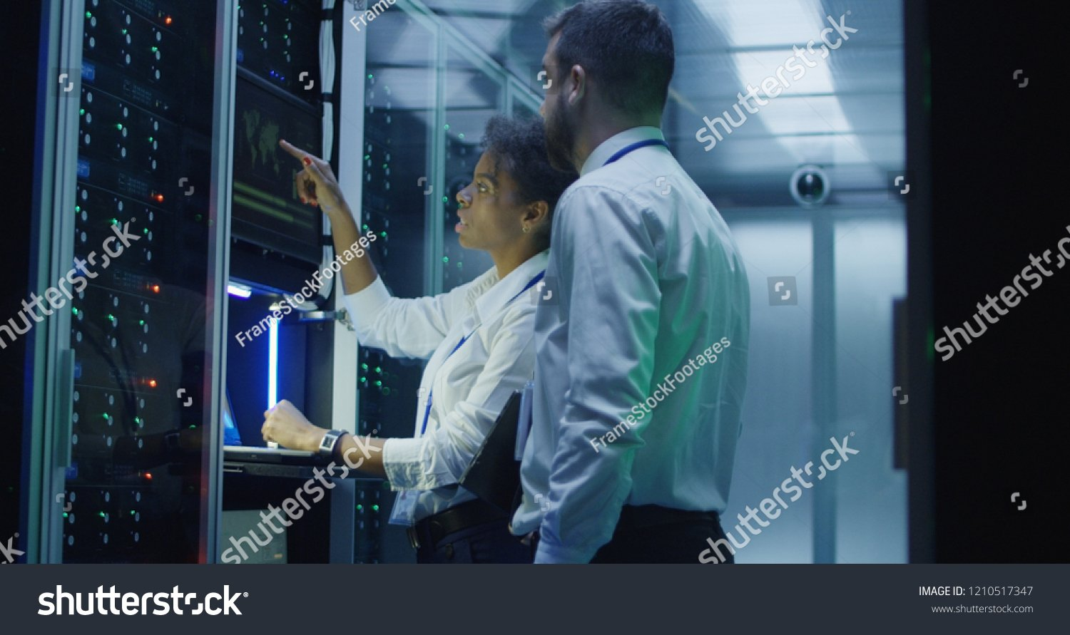 stock-photo-multiethnic-man-and-woman-in-white-shirts-using-laptop-and-tablet-while-working-in-server-room-of-1210517347